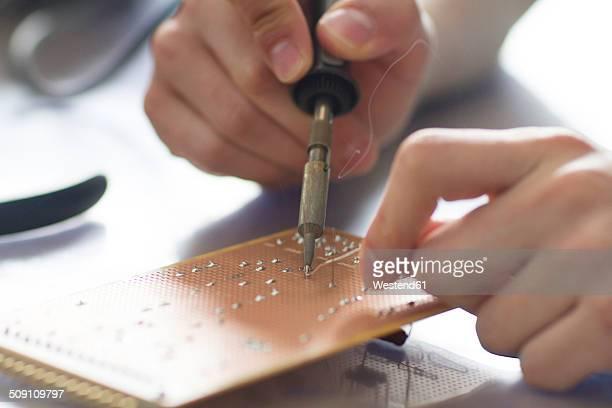 Electronic apprentice soldering circuit board at workshop, detail