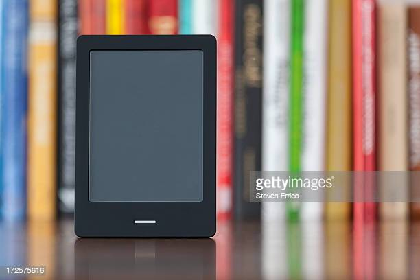 Electronic book reader in front of bookshelf