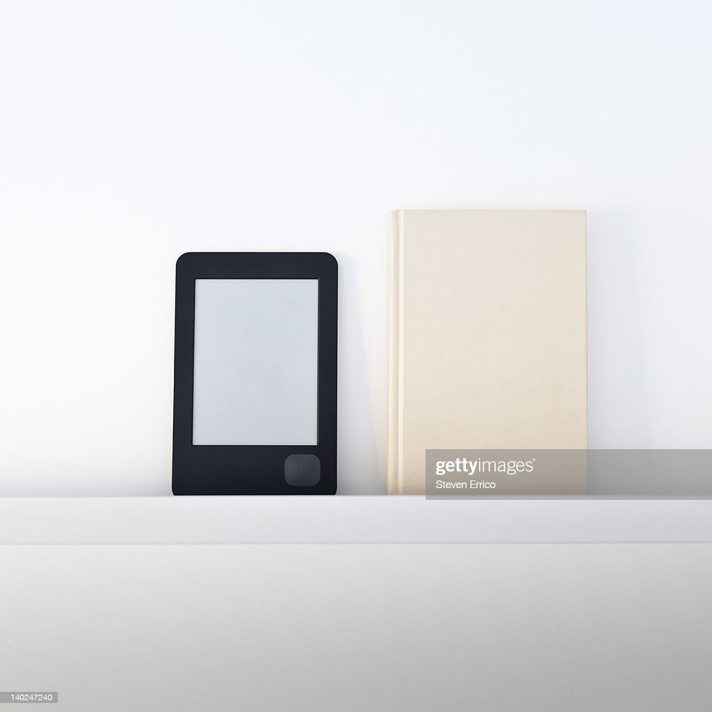 Electronic book reader next to a traditional book : Stock Photo
