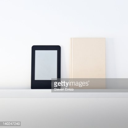 Electronic book reader next to a traditional book : Stockfoto