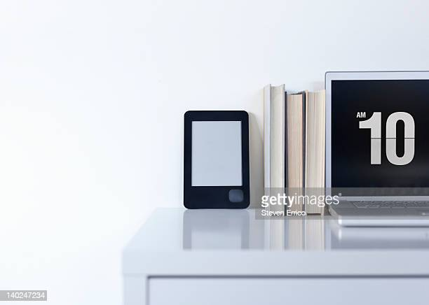 Electronic book reader on desk with other books