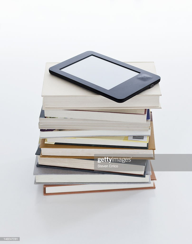 Electronic book reader on stack of books : Stock Photo