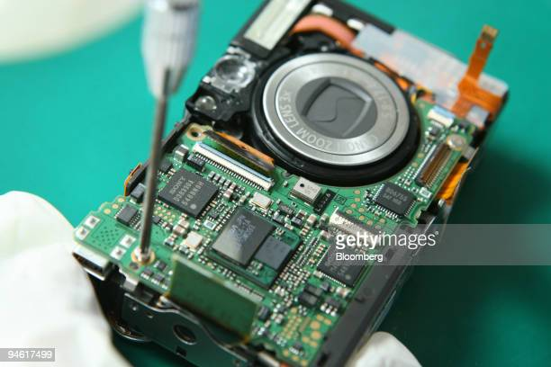 Electronic chips are installed in a compact digital camera at Canon in Petaling Jaya Malaysia on Monday Jan 7 2008 Malaysia's export growth probably...