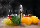 Electronic cigarette, bottles with vape liquid, lemons and fake bunch of grapes within vapor on granite surface and black background