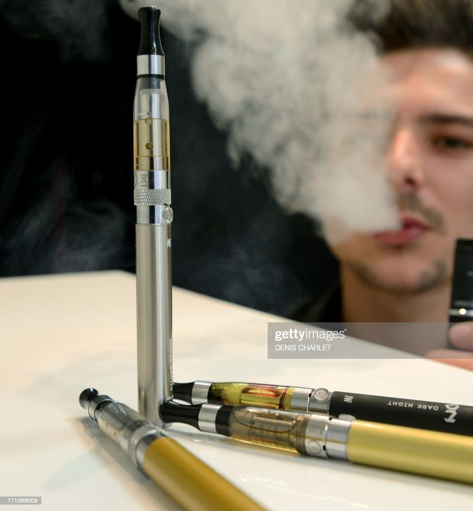 Electronic cigarettes are displayed near a person smoking an electronic cigarette in Lille on June 21, 2013. France said on May 31, 2013 that it would apply the same bans to electronic cigarettes as it does to tobacco but would not completely outlaw the popular smokeless product.