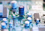 Electronic microcircuit with microchips and capacitors taken closeup. Shallow depth of focus.