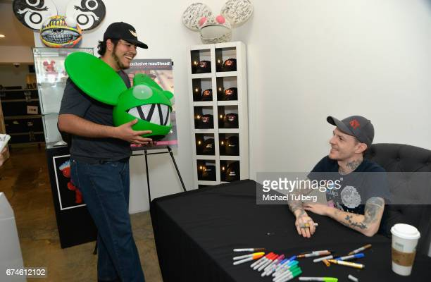 Electronic musician deadmau5 greets a fan carrying a deadmau5 head at deadmau5 and FANCYcom's popup shop 'Lots Of Stuff In A Store' on April 28 2017...