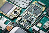 electronic parts of old mobile phone with semiconductor parts and precious metals close-up on green background