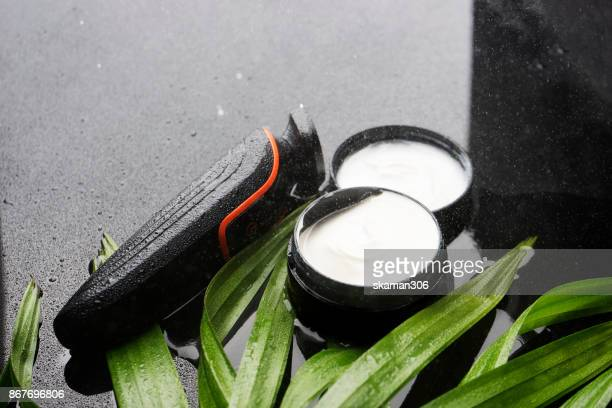 electronic shaving with cream aftershave on green leaves and wet background