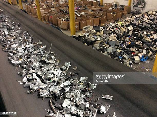 Electronic waste rushed metal parts travel on a conveyer belt from electronic recyclable waste at the Electronic Recyclers International plant in...