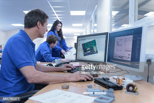 Electronics designers with CAD imagery in electronics factory