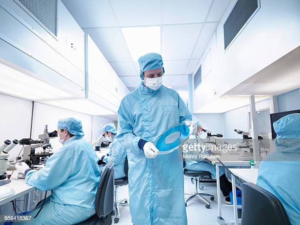 Electronics worker in clean room holding silicon wafer