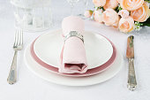Beautifully decorated table with white and pink plates, glasses, silverware, pink napkin and flowers on luxurious tablecloths