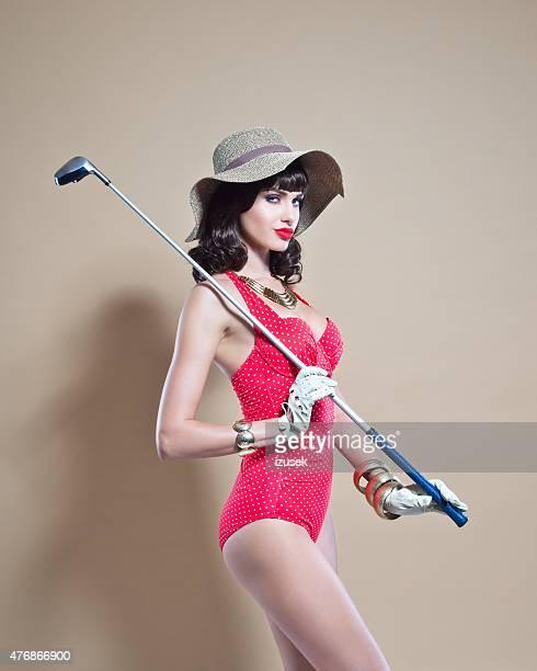 エレガントなスイムスーツを着ている若い女性を持つ sunhat ゴルフスティック