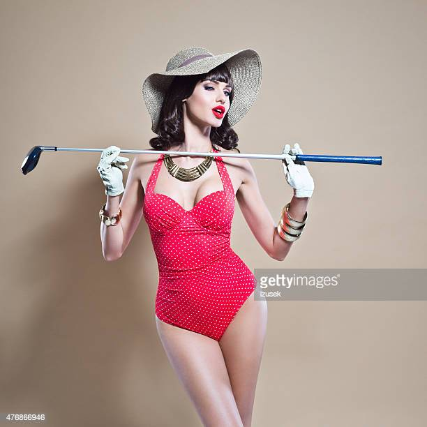 Élégant jeune femme en maillot de bain et sunhat tenant un bâton de golf
