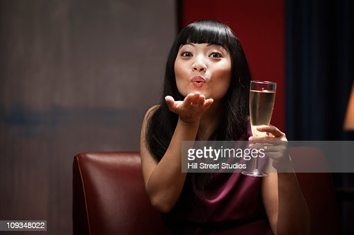 Elegant Asian woman drinking Champagne and blowing a kiss