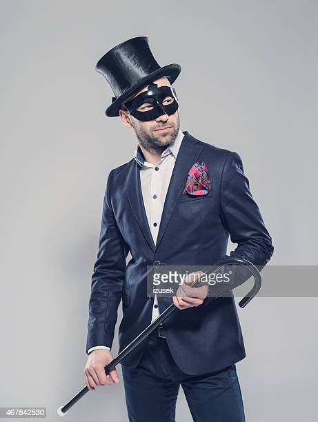 Elegant bearded man wearing top hat and carnival mask