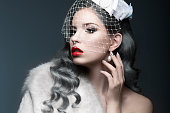 Elegant beautiful girl with silver curls and a veil. Winter image. Beauty face. Picture taken in the studio on a gray background.