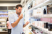 Elegant man choosing perfume in retail store. Casual man testing and buying gift for his lady in a beauty store.