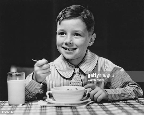 Elegant boy (6-7) eating at table, (B&W), portrait