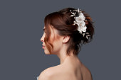 Elegant bride with brown short hair updo and bare shoulders white wedding dress