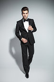 Elegant business man fixing his collar while walking on studio background.