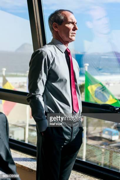 Elegant businessman looking through window