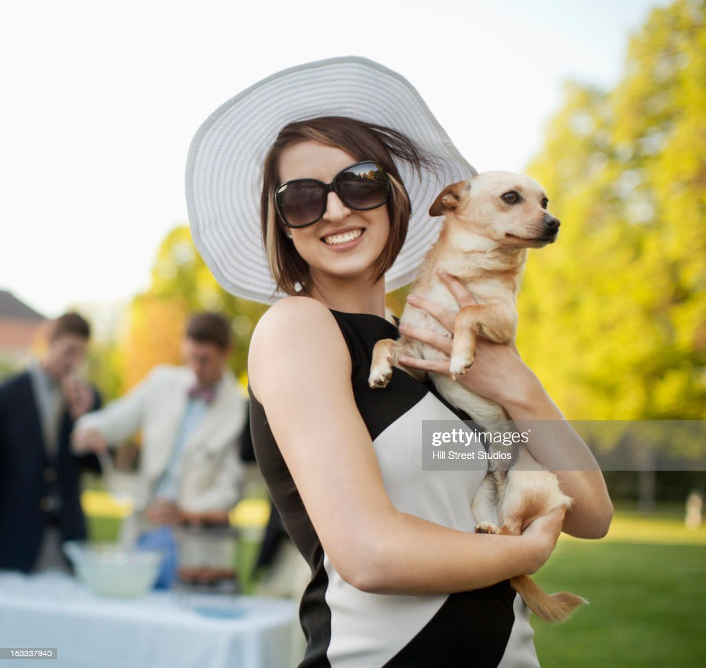 Elegant Caucasian woman holding small dog