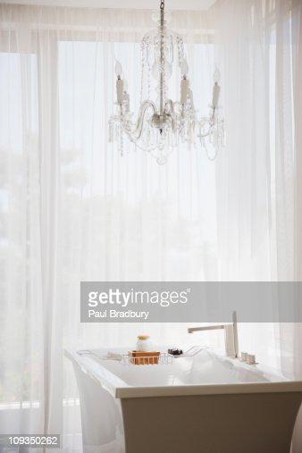 Elegant chandelier and modern bathtub in bathroom : Stock Photo