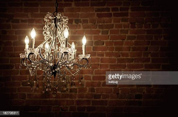 Elegant chandelier with candles in an empty brick interior