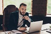 Elegant classic smart clever bearded minded handsome attractive ceo in blazer, jacket, reading, reviewing financial startup project strategy report in laptop at modern workplace, workstation