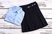 Elegant cotton shirt and skirt. Girls new buttoned blue shirt and pleated skirt with belt for school, top view. Girls school uniform on sale.