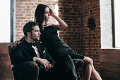 Beautiful young couple in formalwear looking at the window while sitting in a chair together
