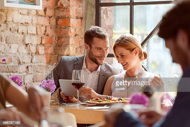 Elegant couple using a digital tablet in the restaurant