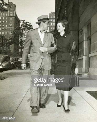 Elegant couple walking on sidewalk, (B&W)