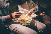 Close-up of chic couple's hands watching television and eating popcorn at night