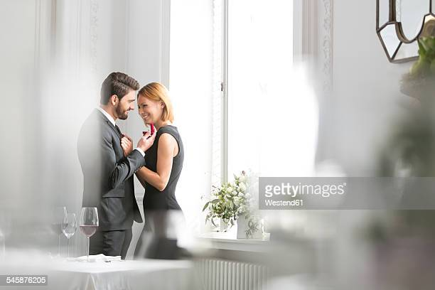 Elegant couple with engagement ring in restaurant