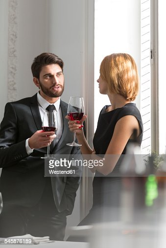 Elegant couple with red wine glasses in restaurant