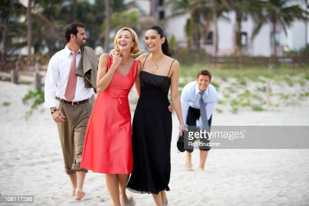 Elegant couples walking on beach together