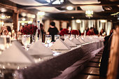 Looking down the table at placesetting with wine glasses, folded