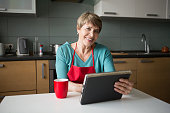 Elegant elderly woman using  tablet in the kitchen