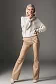 elegant fashionable woman posing in white sweater and beige pants, on grey
