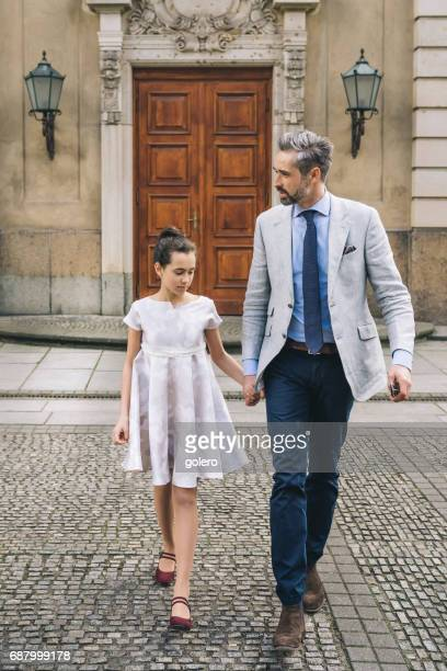 elegant father walking hand in hand with festive dressed teenage daughter