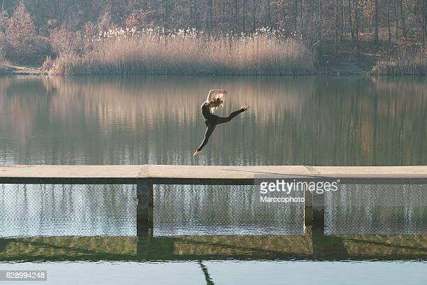 Elegant female ballet dancer performing on bridge across lake