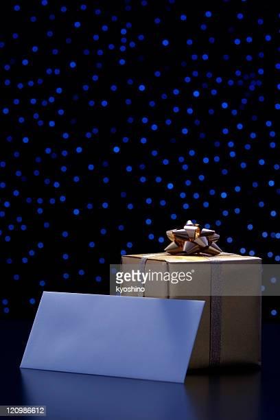 Elegant gift box and blank envelope against blue illumination background