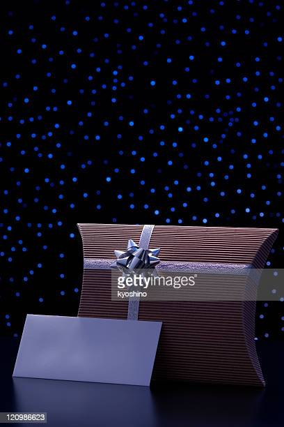 Elegant gift box and blank envelope against blue illumination background