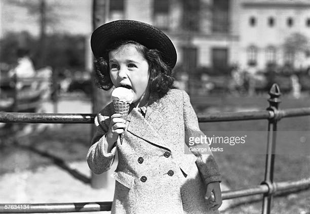Élégante femme (4-5) manger de la crème glacée à l'extérieur, (B & W