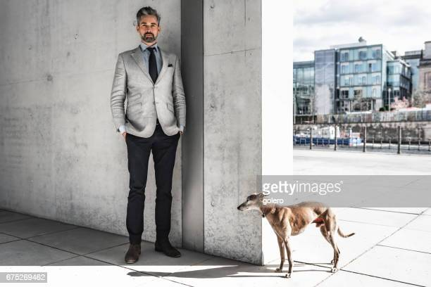 elegant handsome bearded businessman standing with dog  in business district