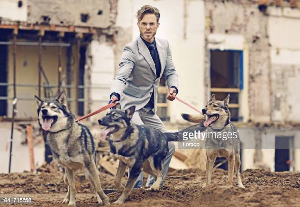 Elegant handsome man with dog pack on a building site