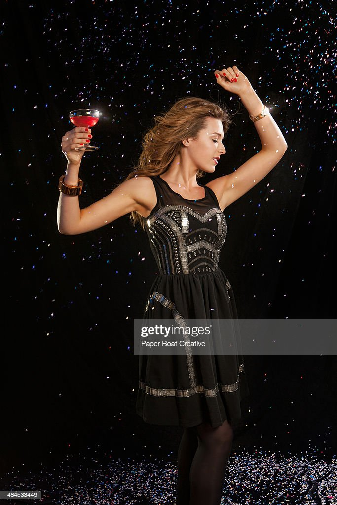 Elegant lady in a black dress dancing in a club